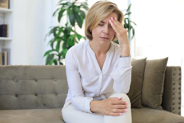 居間のソファーに座っている不幸な中年女性。