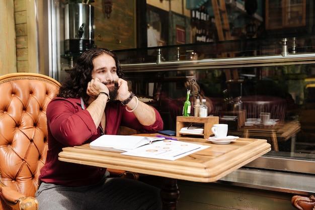Несчастный хороший человек думает о работе, сидя в кафе