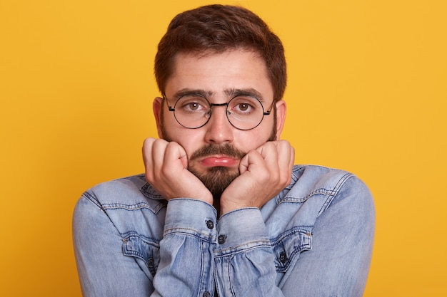 Unhappy offended young bearded male curves lower lip and keeps hand under chin, posing against yellow wall