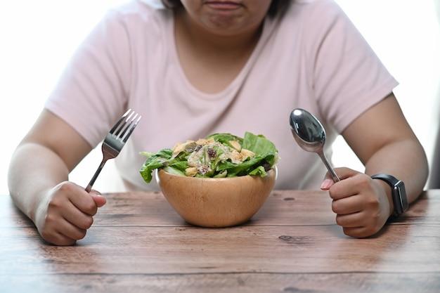 테이블에 앉아서 샐러드 그릇을보고 불행 한과 체중 여자.