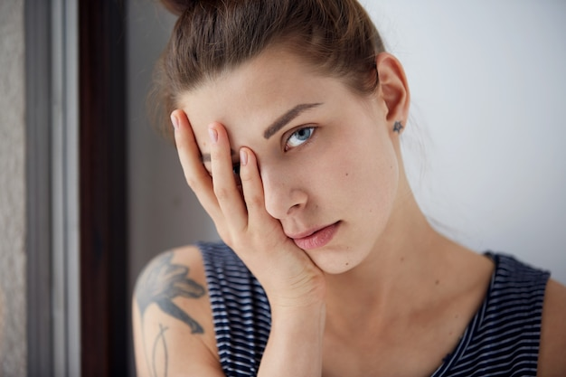 Unhappy overwhelmed girl having headache bad day keeps hands on face