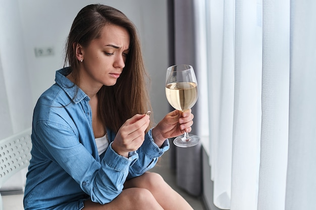 Unhappy pensive drinking divorced woman with wine glass holds gold ring during thinking and worrying about end marriage after break up relationship and divorce