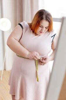 Несчастная пухленькая женщина считает себя толстой, глядя на сантиметровую ленту