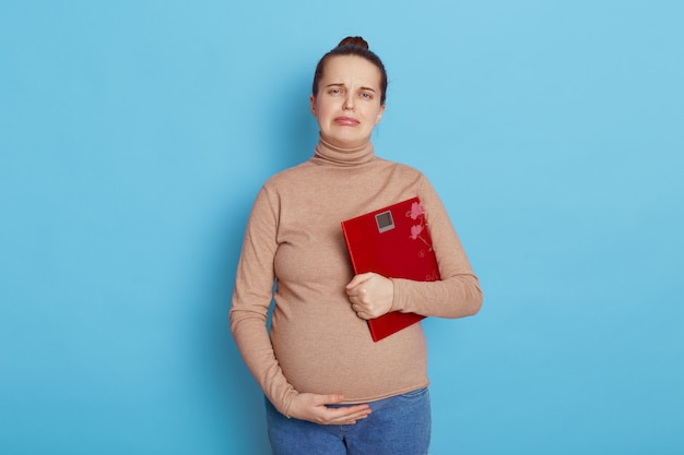Unhappy pregnant woman holding a red scale isolated on blue