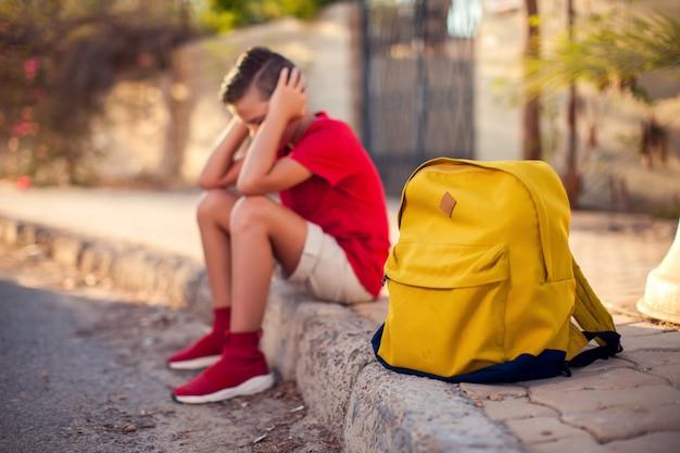 屋外に座っているバックパックで不幸な生徒。ストレスを感じる少年。子供と感情の概念