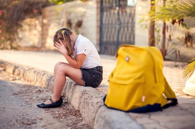 屋外に座っているバックパックで不幸な生徒。ストレスを感じている女の子。子供と感情の概念