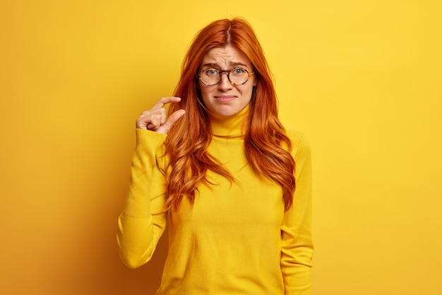 Unhappy redhead woman makes little gesture demonstrates something tiny dressed in casual jumper.