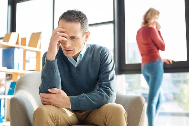 不幸な関係。彼の額を保持し、家で問題を抱えている間彼の関係について考えている悲しい落ち込んでいる不幸な男