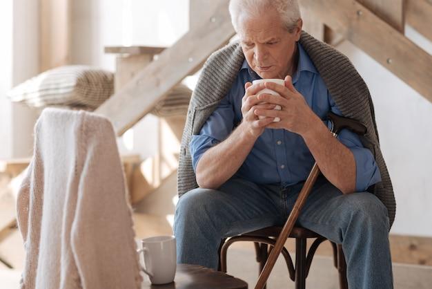Несчастный пенсионер старший мужчина сидит на стуле и пьет чай, глядя на пустое пространство рядом с ним