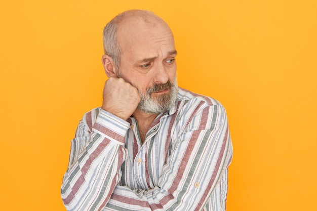 Unhappy retired senior man with gray beard and baldness posing isolated with fist on his cheek