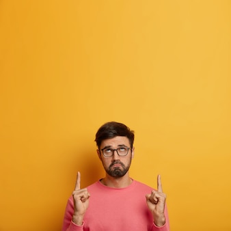 Unhappy sad bearded male in spectacles looks with gloomy expression upwards