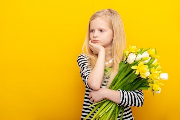 ブロンドの髪を持つ不幸な悲しい少女は春の花束白いチューリップを保持します