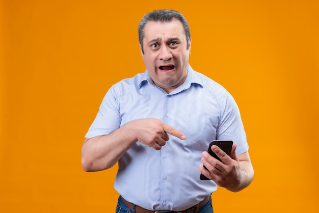 Unhappy sad man in blue vertical striped shirt points his finger to mobile phone while standing on an orange background
