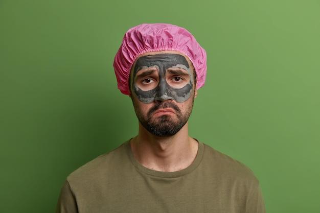 불행한 슬픈 남자는 얼굴 마스크에 불만이 있고, 문제가있는 피부와 얼굴을 돌보는 데 지 쳤고, 회춘 치료를 받고, 목욕 모자를 쓰고, 녹색 벽에 고립되어 있습니다. 남성 성, 아름다움, 스파