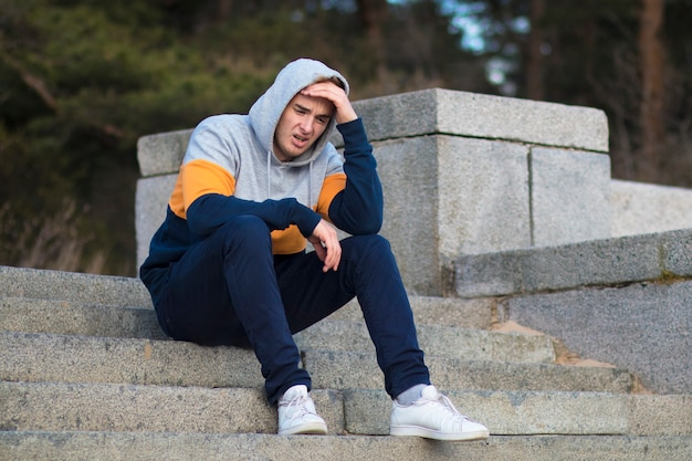 Unhappy sad upset depressed guy crying, young lonely frustrated desperate man sitting on stairs in hood, suffering because of bad mood, problems, emotional pain. broken heart, failure concept.