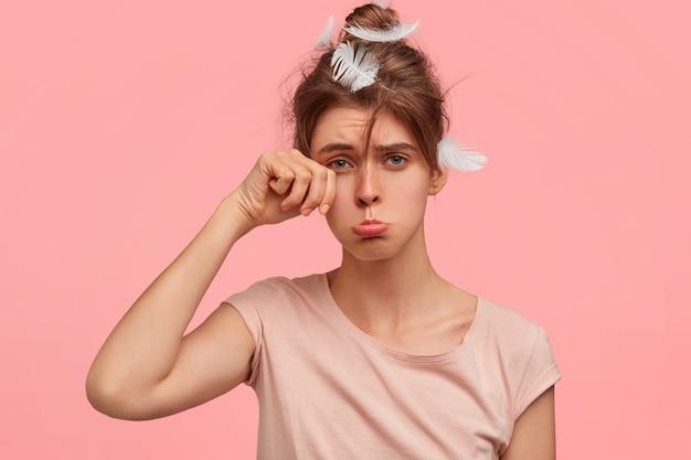 Несчастная грустная женщина трет глаза и поджимает нижнюю губу, имеет сонное выражение лица, недовольна тем, что не выспалась этой ночью.