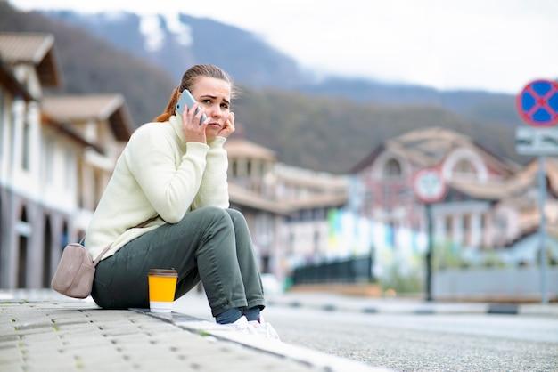 불행한 슬픈 여자는 길가에 있는 보도에 앉아 스마트폰으로 말하는 휴대폰 소녀에 대해 말한다