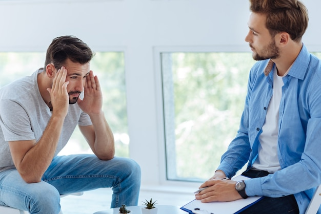 불행한 슬픈 젊은이가 그의 심리학자 반대편에 앉아 인생에서 너무 많은 스트레스를 받으면서 그의 머리를 잡고