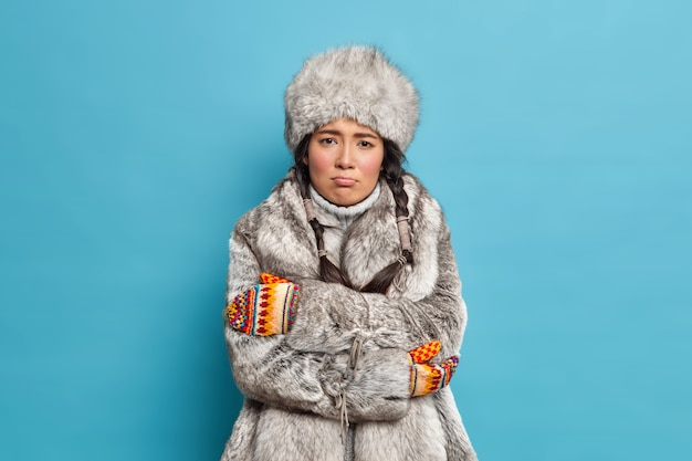 Unhappy scandinavian woman in fur hat and coat crosses hands and feels freezing trembles during severe frosty day wears winter outerwear