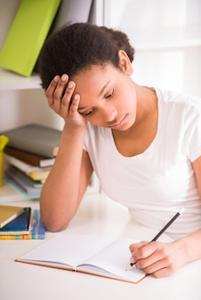 Unhappy schoolgirl sitting at table and writing homework.
