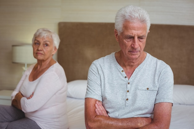 Unhappy senior couple after arguing while sitting on bed
