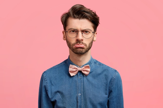 Unhappy serious unshaven young male with sullen expression, expresses antipathy, wears denim shirt with pink bowtie, dislikes something. stylish businessman shows negative emotions after failure