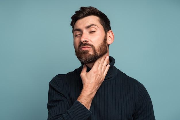 목을 만지는 불행한 남자는 삼키는 동안 통증, 질식, 인후 염증, 인후염의 결과입니다. 파란색 배경에 고립 된 실내 스튜디오 촬영