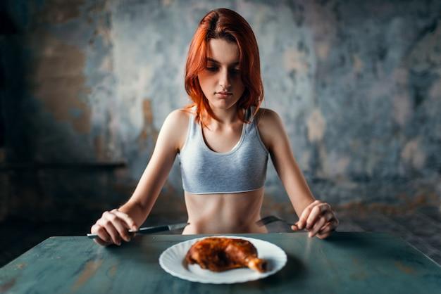 Несчастная тощая женщина против тарелки с едой, отсутствие аппетита. концепция сжигания жира или калорий. похудание, анорексия