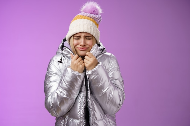 Unhappy sobbing whining cute blond girl pull jacket tight body close eyes crying freezing cold standing snowy winter resort shaking low temparature, purple background suffering discomfort.