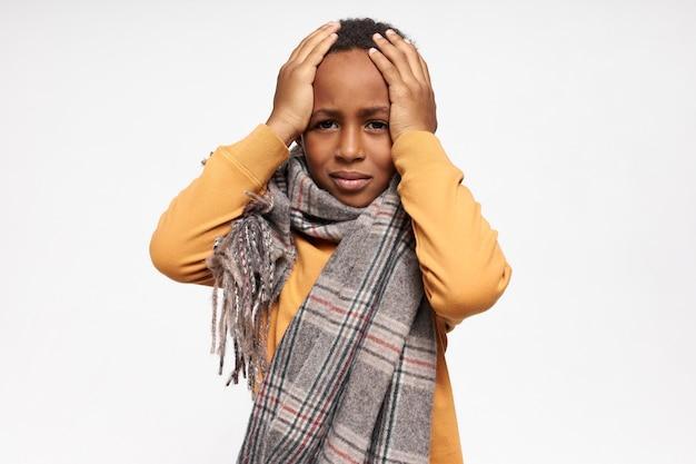 ひどい頭痛や片頭痛に苦しんでいる彼の頭に手をつないで病気になっている不幸な強調されたアフリカ系アメリカ人の少年