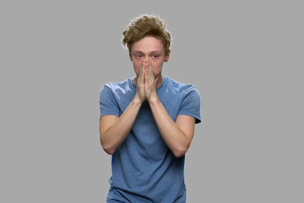 회색 배경에 불행 스트레스 십 대 소년입니다. 얼굴에 손을 잡고 우울 된 십 대 소년입니다.