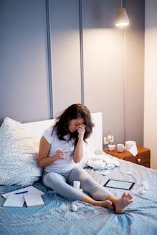 Несчастные подчеркнутые женщины, лежащие на кровати с болью в голове, держа лекарства и стакан воды