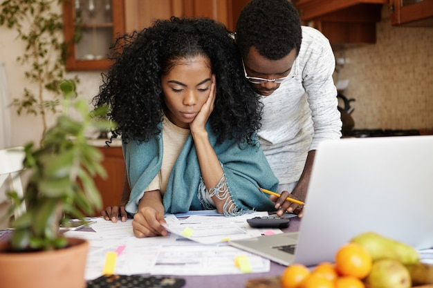 Unhappy and stressed young african woman sitting at kitchen table with papers and notebook computer, trying to cut amount of domestic expenses while doing family budget together with her husband