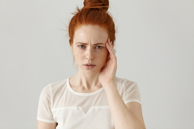 Unhappy stressed young redhead female with hair knot touching face while suffering from bad headache, frowning and looking with tensed and painful expression on her face. body language