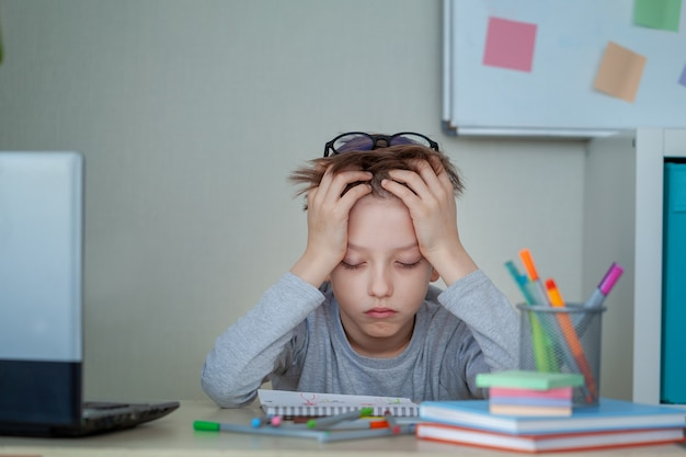 Unhappy and strssed school boy studying with a notebooks on his desk at home. child is tired of online learning. education and childhood concept