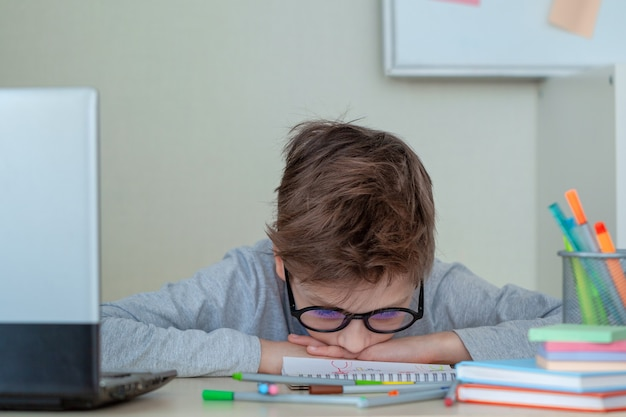 Unhappy and strssed school boy studying with a notebooks on his desk at home. child is tired of online learning. kid rests face down on table. education and childhood concept