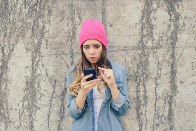 彼女のボーイフレンドの携帯電話でsmsを読んで不幸な驚きの悲しい嫉妬深い女性。