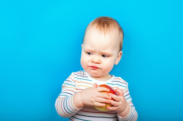 Unhappy thoughtful child with apple on blue background pensive baby and first feeding complementary feeding of child nutritional interest food allergy