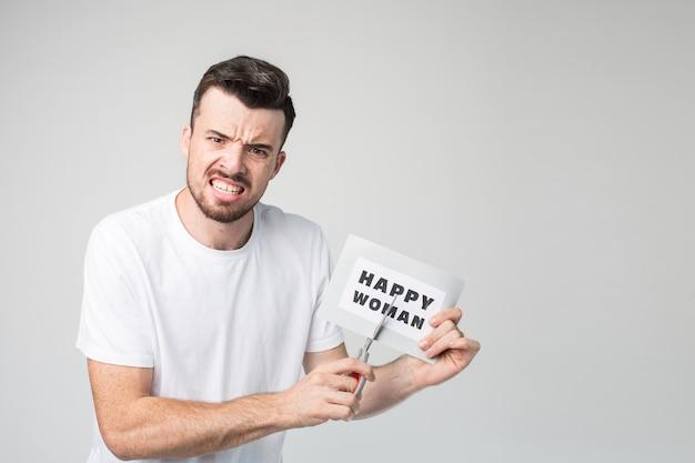 一枚の紙の幸せな女性を指して、目を細めて不幸な思いやりのある感情的な男。痛い写真。