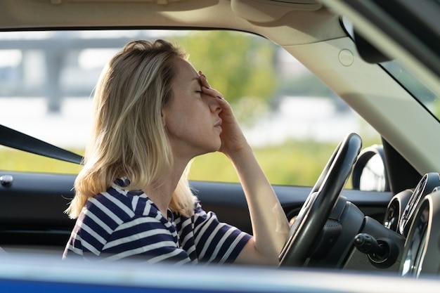 頭痛に苦しんで車の運転に座っている不幸な疲れた女性ドライバーが鼻と額に触れる