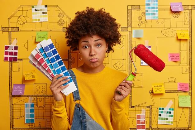 불행한 피곤한 젊은 여성은 수리, 색상 샘플, 벽화 또는 보수 후 피로를위한 도구를 보유하고 있으며 창의적인 디자인 프로젝트를 통해 포즈를 취합니다. 집 수리 또는 재건 작업 개념.