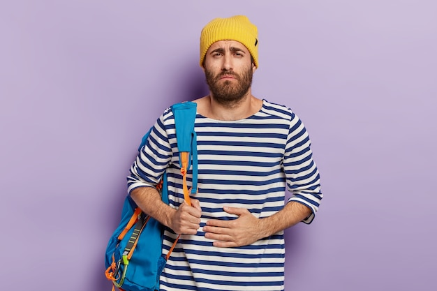 Unhappy traveler holds hand on stomach, suffers from painful cramps, carries tourist backpack, ate something not fresh, has displeased facial expression, has problem with health during long trip