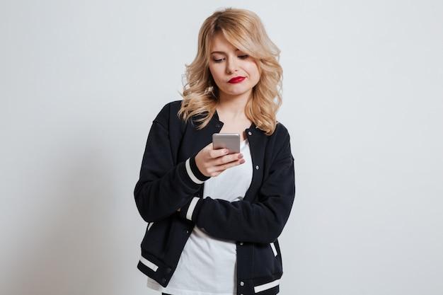 Несчастная расстроенная молодая женщина читает сообщение на свой мобильный телефон