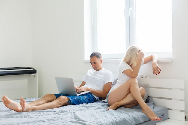 Unhappy woman because his husband working in bed, relationship problems