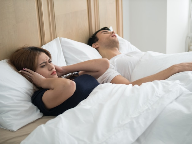 Unhappy woman covering ears while man snoring in bed at home