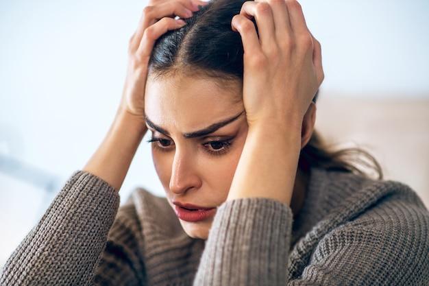 Несчастная женщина. темноволосая молодая женщина выглядит напряженной и несчастной