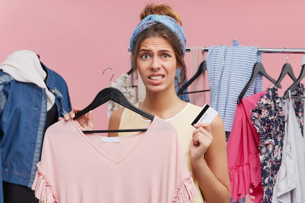 Unhappy woman doing shopping, standing in clothes shop, holding new dress and credit card, being shot of money, having financial crisis, wanting to buy new clothes immediately. shopping expanses