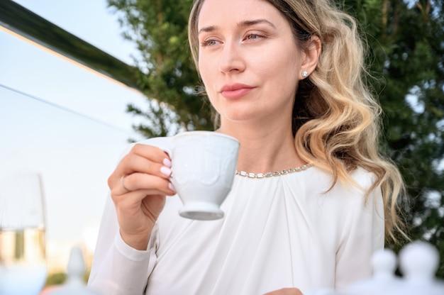 Несчастная женщина пьет чашку кофе