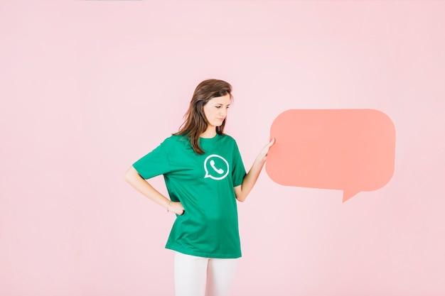 Unhappy woman holding empty orange speech bubble on pink background
