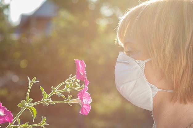 野花の花束を保持し、花粉に対するアレルギーと戦おうとしている保護マスクの不幸な女性。アレルゲンから鼻を守る女性。アレルギーの概念。